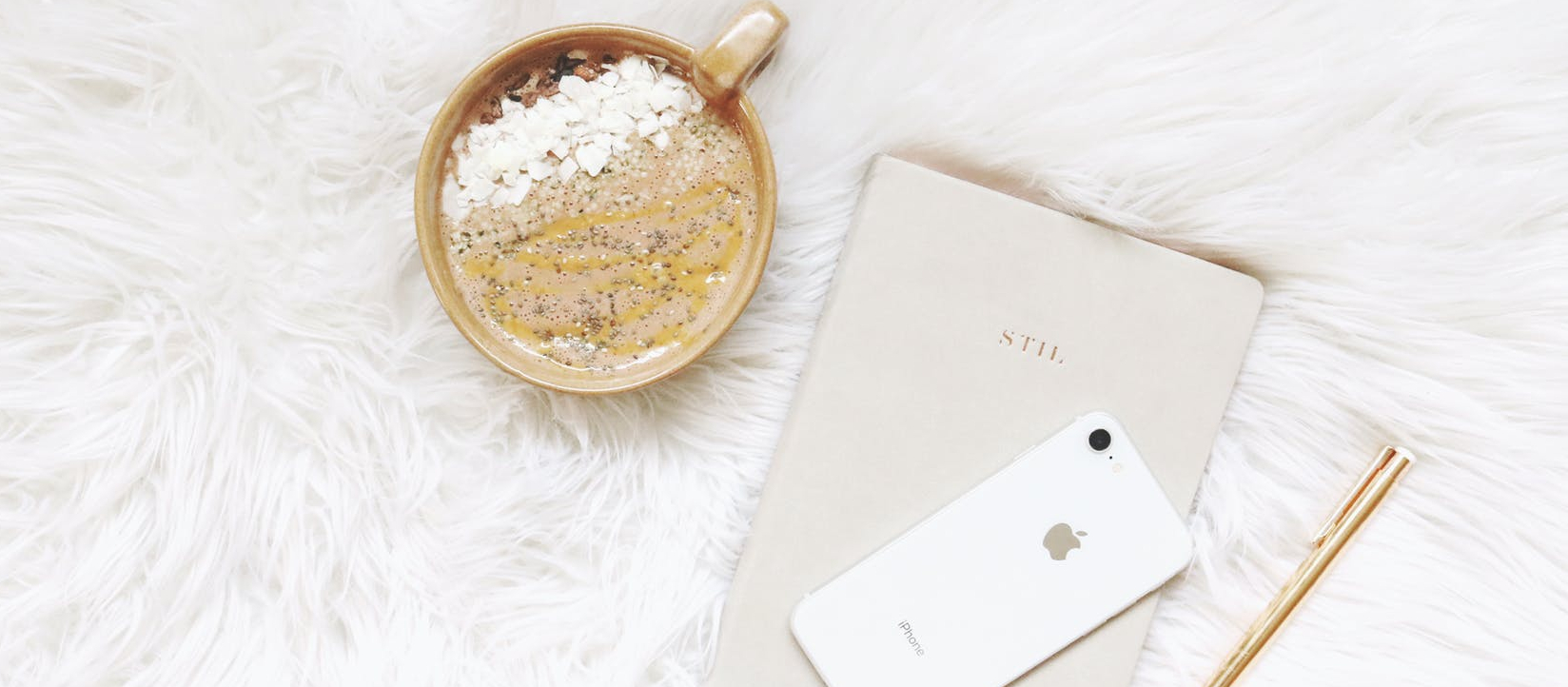 white iphone gold colored pen and round gold colored cup